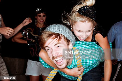 Young friends giving piggybacks at party