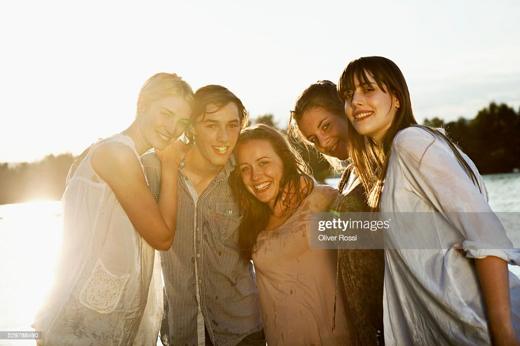 Young friends hanging out by a lake : Foto de stock