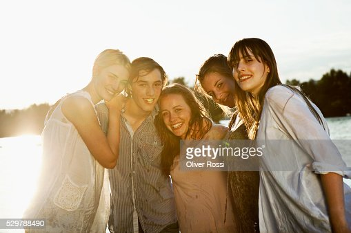 Young friends hanging out by a lake : Stock Photo