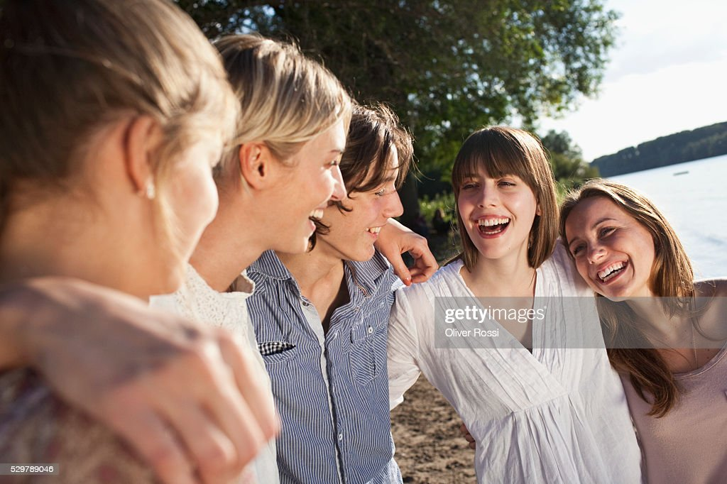 Young friends hanging out by a lake : Stockfoto