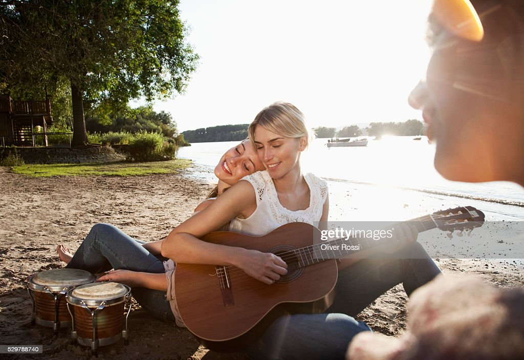 Young friends hanging out on a beach : Foto de stock
