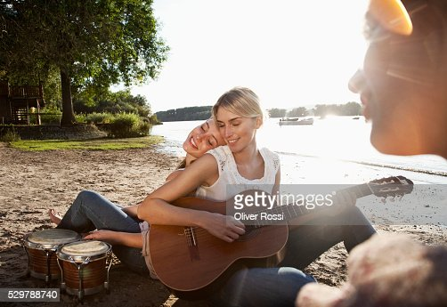 Young friends hanging out on a beach : Stockfoto