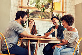 Young friends having a great time in restaurant. Group of young people sitting in a coffee shop and smiling.