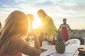 Young friends having barbecue party at sunset on top of the roof - Happy people doing bbq dinner outdoor - Focus on woman smiling - Food, fun and friendship concept - Warm filter