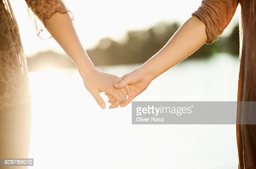 Young friends holding hands : Stock Photo