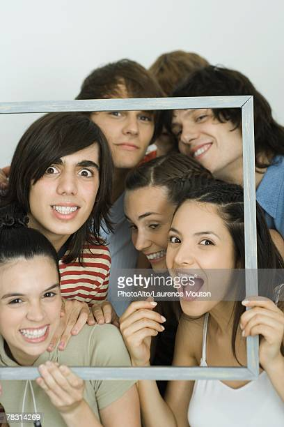 Young friends holding up frame together, smiling at camera