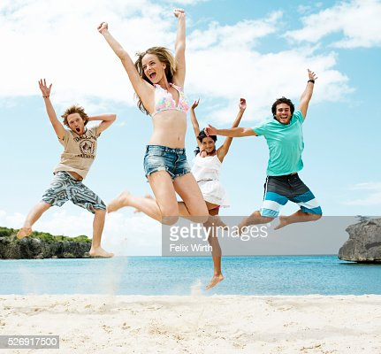 Young friends jumping on beach : ストックフォト