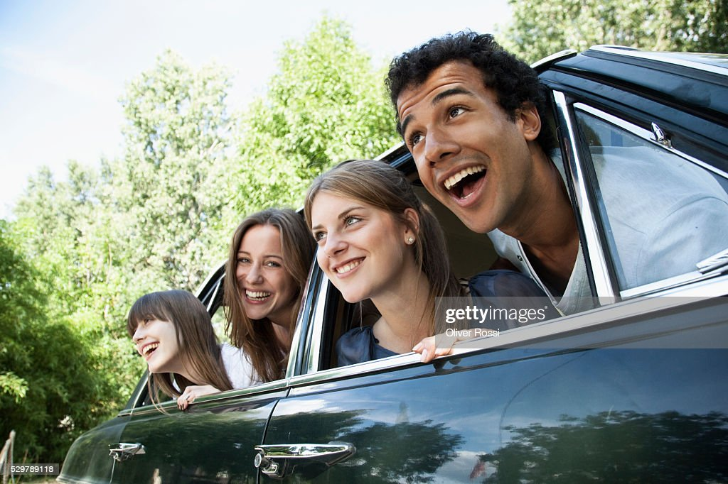 Young friends leaning out car windows : Stock Photo