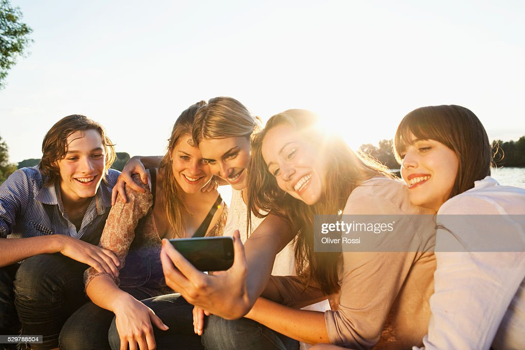 Young friends looking at a picture : Foto de stock