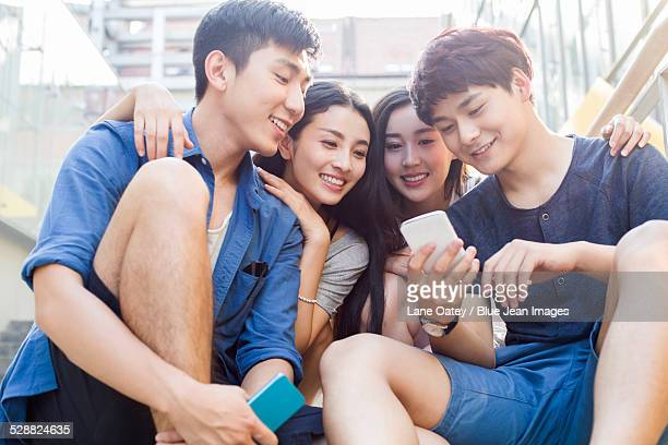 Young friends looking at a smart phone