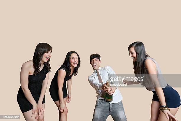 Young friends opening champagne bottle over colored background