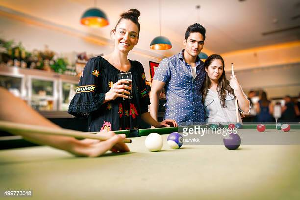 Young friends playing billiard in the pub