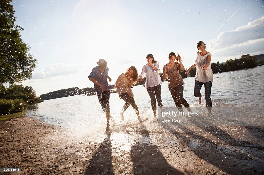 Young friends playing in a lake : Bildbanksbilder