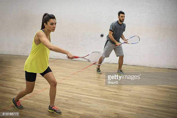 Young friends playing squash together on a court.