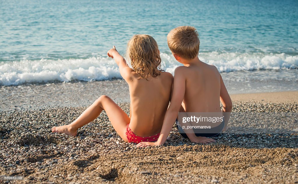 Young friends portrait at the beach looking at the sea. : Stock Photo