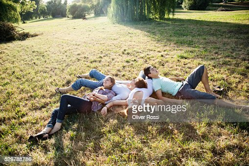 Young friends relaxing in the grass : Stock Photo