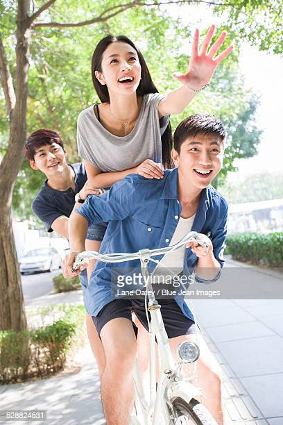 Young friends riding bicycle at campus