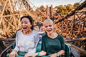 Shot of young friends riding roller coaster ride at amusement park. Young people having fun at amusement park.