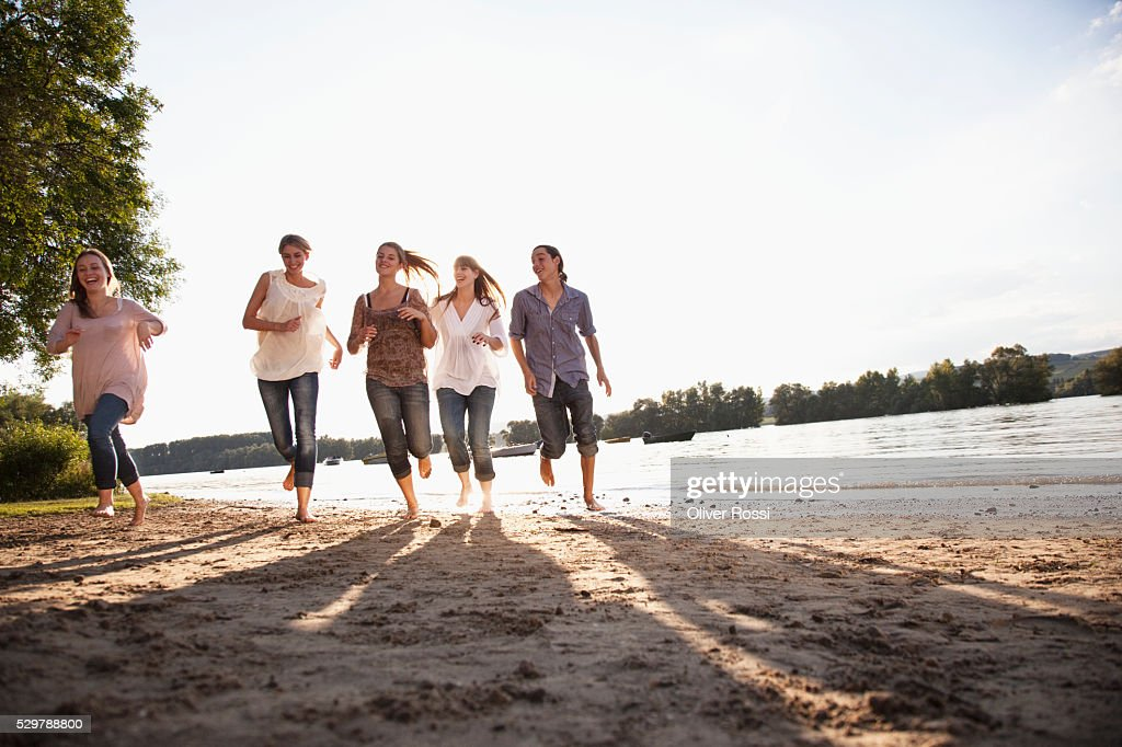 Young friends running beside a lake : Stock Photo