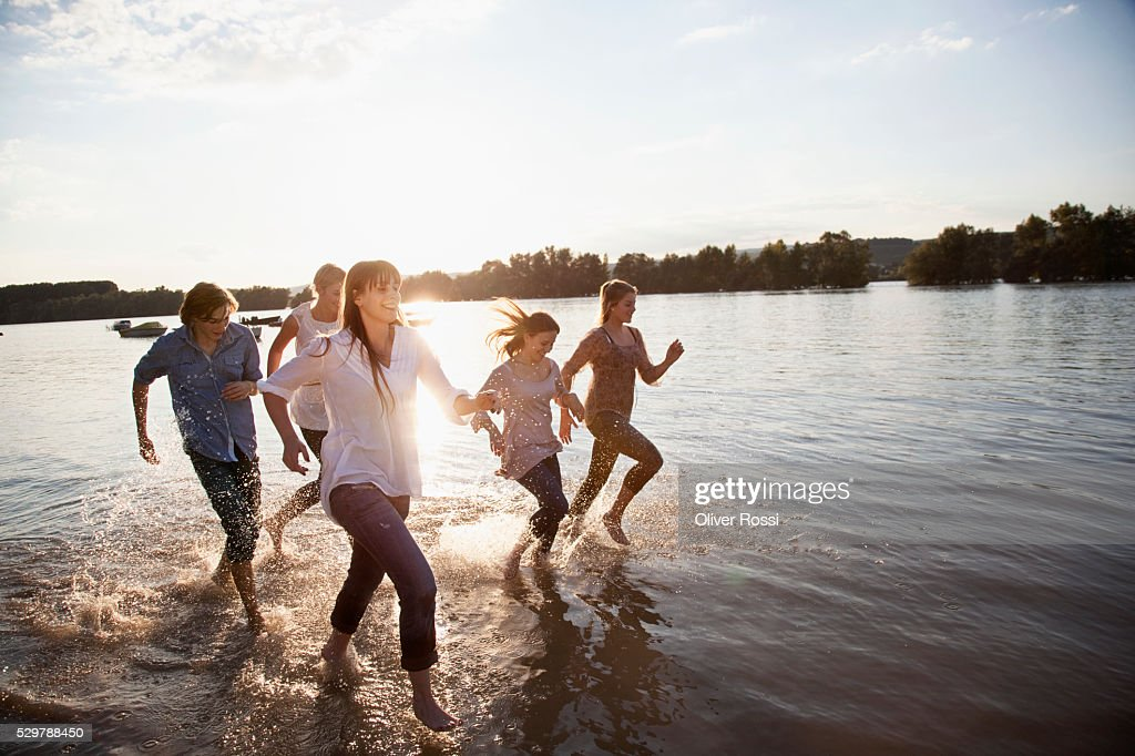 Young friends running in a lake : Foto de stock