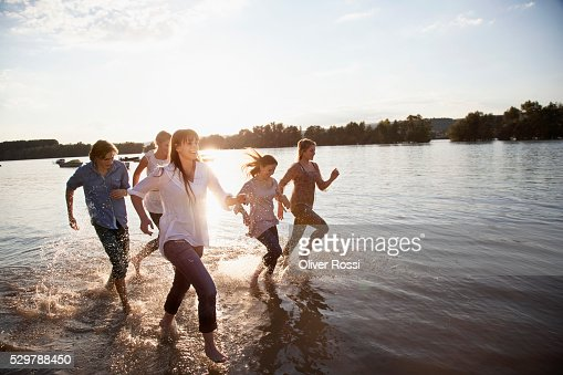 Young friends running in a lake : Stock Photo