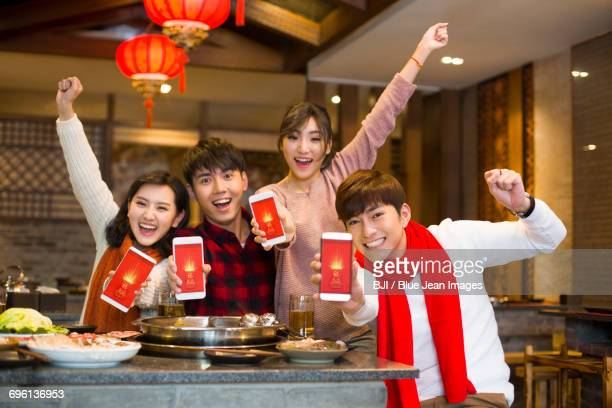 Young friends showing smart phones in restaurant