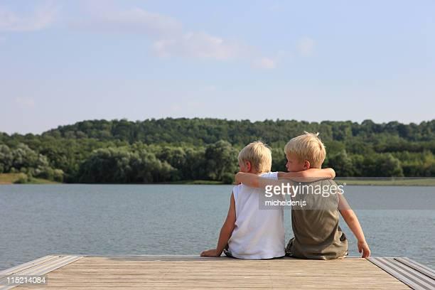 Jeunes amis, assis dans la jetée