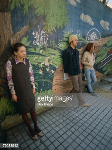 Young friends standing against painted wall : Stock Photo