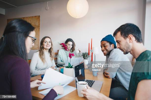 Young friends studying together in college dorm room