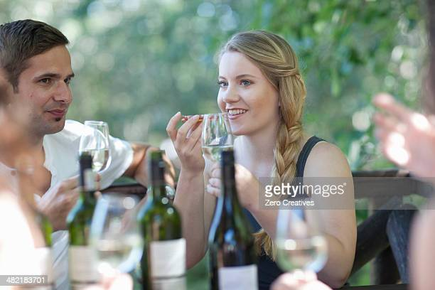 Young friends tasting and smelling wine at vineyard bar