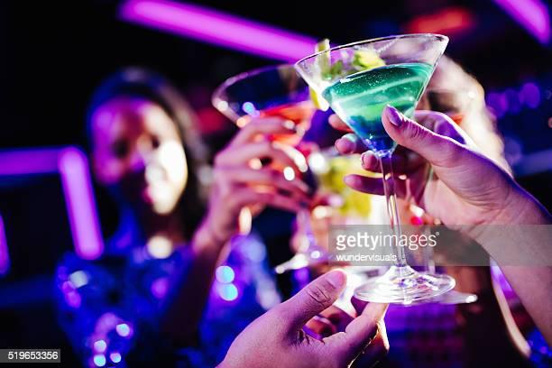 Jóvenes amigos brindis con bebidas de cortesía durante la fiesta del Club de noche