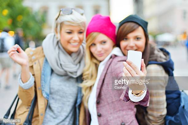 Young friends together taking selfies