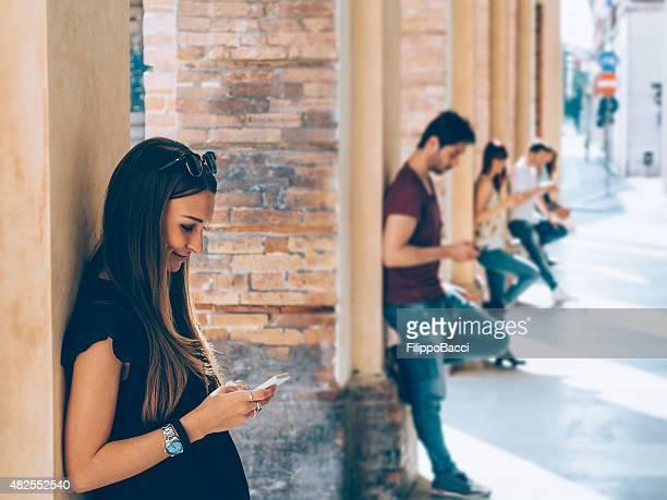 Junge Freunde mit Handy im Freien