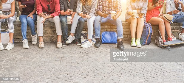 Young friends using smartphones and drinking coffee outdoor - Group of people having fun with technology trends - Youth, new generation addiction and friendship concept - Main focus on center guys : Foto de stock