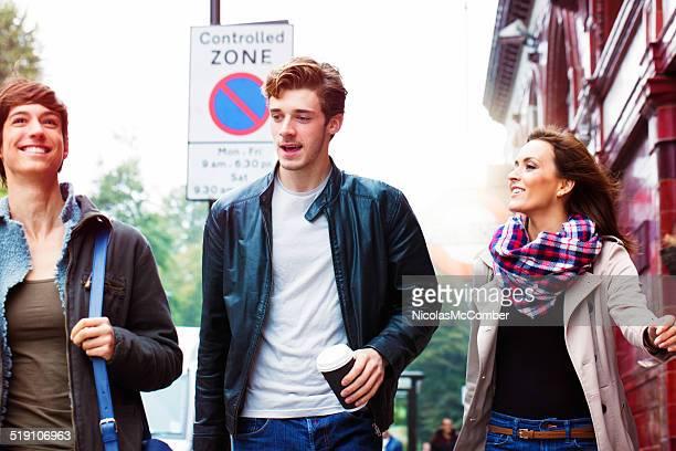 Jeunes amis marchant dans la rue souriant