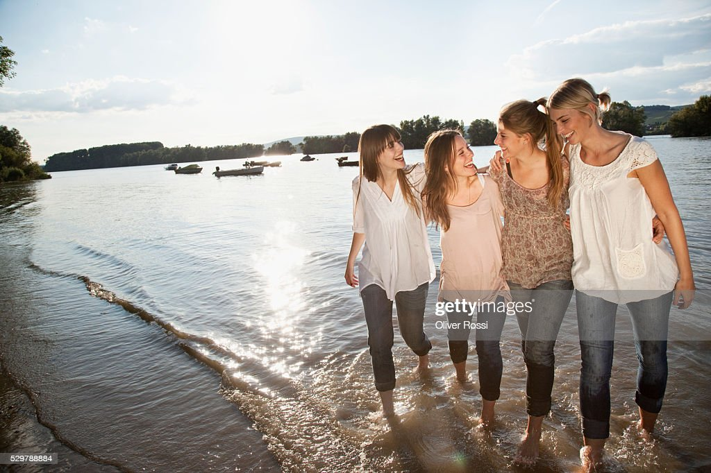 Young friends walking in the water : Foto de stock