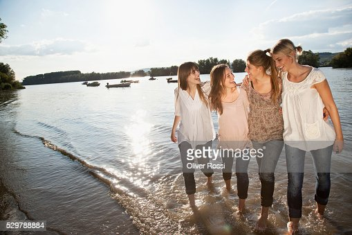 Young friends walking in the water : Stockfoto