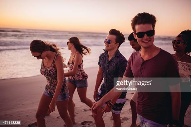 Jeunes amis marchant sur la plage après le coucher du soleil