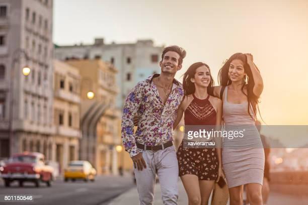 Junge Freunde gehen auf Bürgersteig während des Sonnenuntergangs