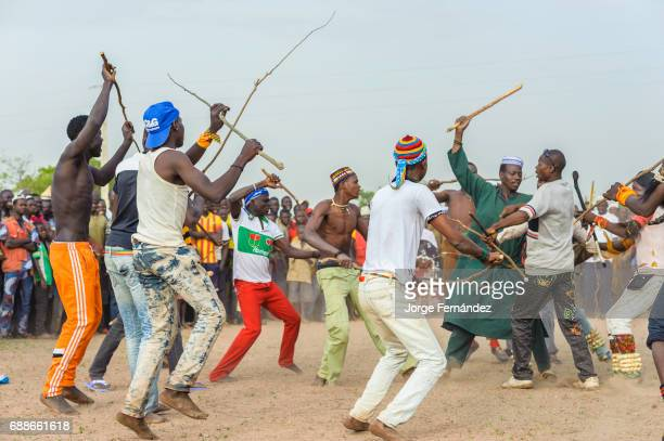 Young Fulani men fight with sticks in front of a big crowd Fulani men from this area have to endure a harsh initiation rite before being considered a...