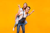 Young funny cheerful joyful couple, boyfriend piggy backing girlfriend, girl showing peace signs with her hands over yellow background, isolated