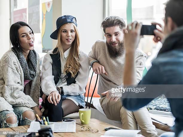 Jeune drôle personnes photographiées par leur ami au café.