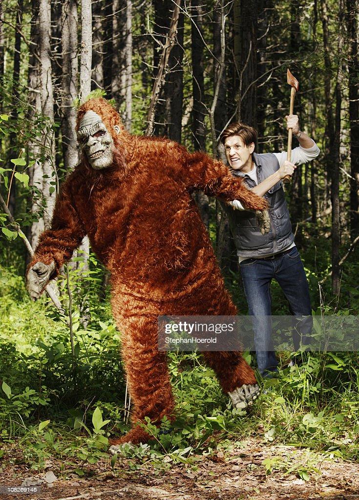 Young, furious man chasing a sasquatch (bigfoot) with an axe
