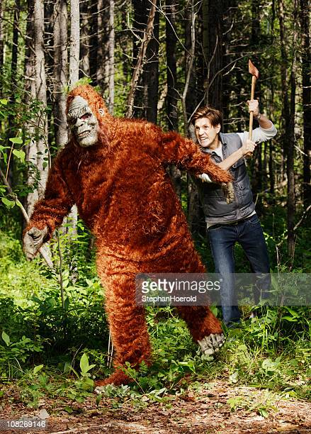 Young, furious man chasing a sasquatch (bigfoot) with an axe