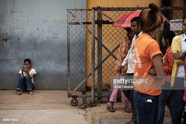 A young garment worker sits while using her mobile phone during a demonstration inside the Canadia Industrial Park demanding an increase of the...