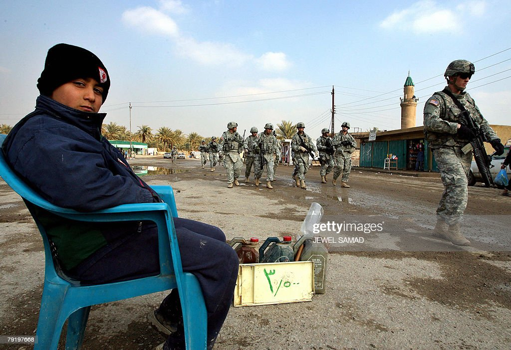 A young gasoline vendor watches as US soldiers from the 6th Squadron, 8th Cavalry Regiment patrol a market place in southern Baghdad, 24 January 2008. A suicide bomber disguised as a policeman killed the provincial police chief for Iraq's main northern city of Mosul today as he visited the scene of an earlier blast in which 34 people died, police said. AFP PHOTO/Jewel SAMAD