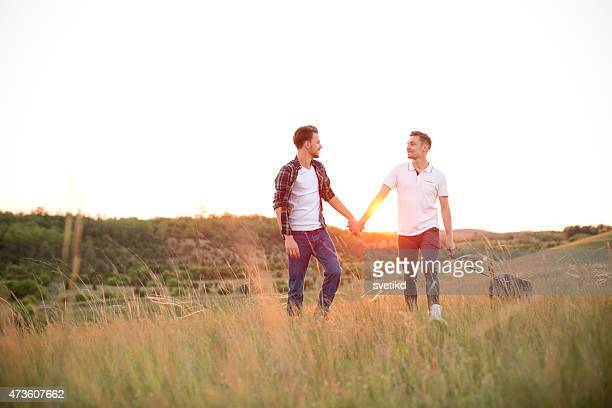 Young gay couple in a meadow.
