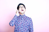 Young Geeky  Man in colorful shirt laughing on the phone