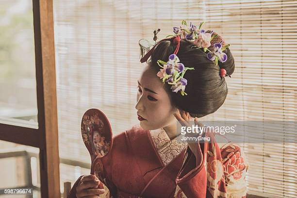 Young geisha woman adjusting hairstyle with hand mirror