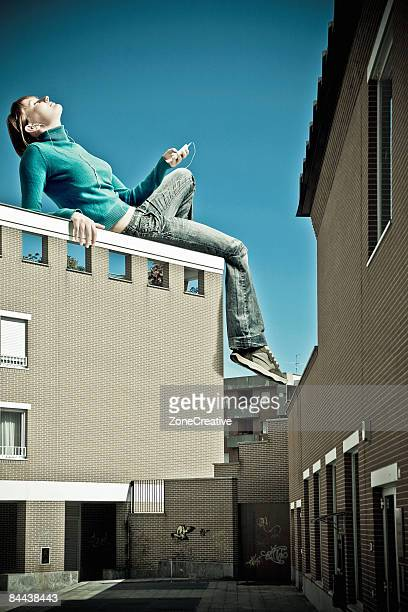 Young giant girl listens to music over a building